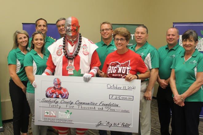 """Jon """"Big Nut"""" Peters and his wife, Terese, pose with board trustees and staff members of the Sandusky County Communities Foundation Wednesday after donating $25,000 to the foundation. SCCF announced its 2021 grant awards earlier Wednesday at Terra State Community College's Neeley Center."""
