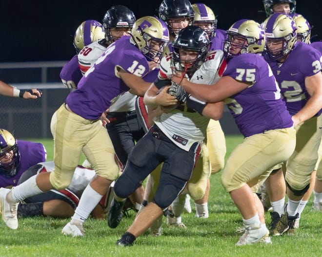 Fowlerville's Austin Barbour hauls down St. Johns Josh Pagels in the Gladiators 27-20 loss Friday, September 10, 2021 in Fowlerville.