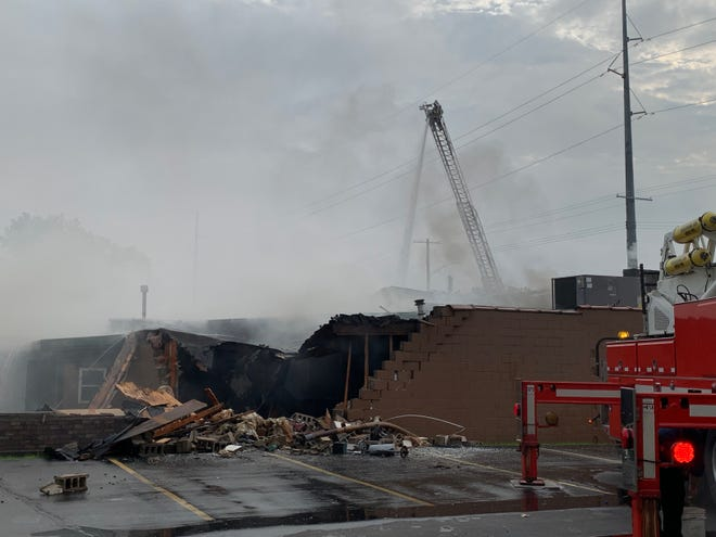 Firefighters continue work to control the blaze at the Dispatch Sports Pub & Grill on Thursday morning, October 14, 2021.. Lansing Township firefighters were called to the site about 4:30 a.m.
