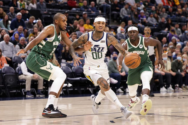 Jazz guard Jordan Clarkson tries to dribble away from Bucks forward Khris Middleton during the first quarter Wednesday night.