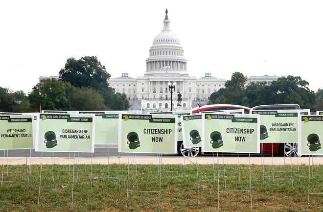 Los inmigrantes instalan cientos de carteles de tarjetas verdes que simbolizan su demanda de ciudadanía estadounidense frente al edificio del Capitolio de los Estados Unidos el 13 de octubre de 2021 en Washington, DC.