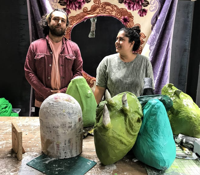 Artists Manuel Urueta and Celina Galicia create papier-mache artworks. Some works in progress by the couple are shown before them. They also create videos.