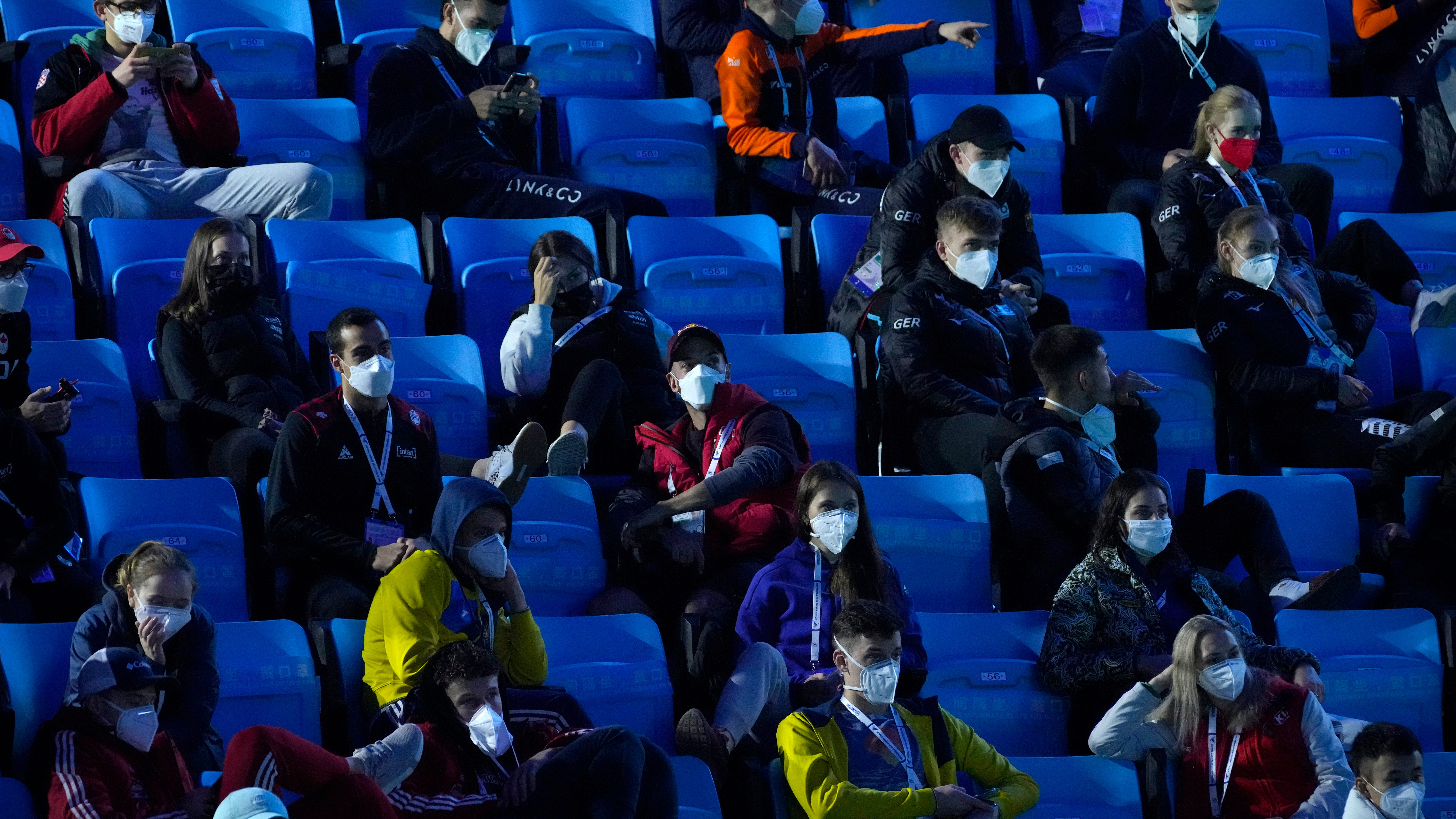Athletes wearing face masks to protect against COVID-19 and sitting distanced from each other watch the action at the ISU World Cup Short Track speed skating competition, a test event for the 2022 Winter Olympics, at the Capital Indoor Stadium in Beijing, Sunday, Oct. 24, 2021.