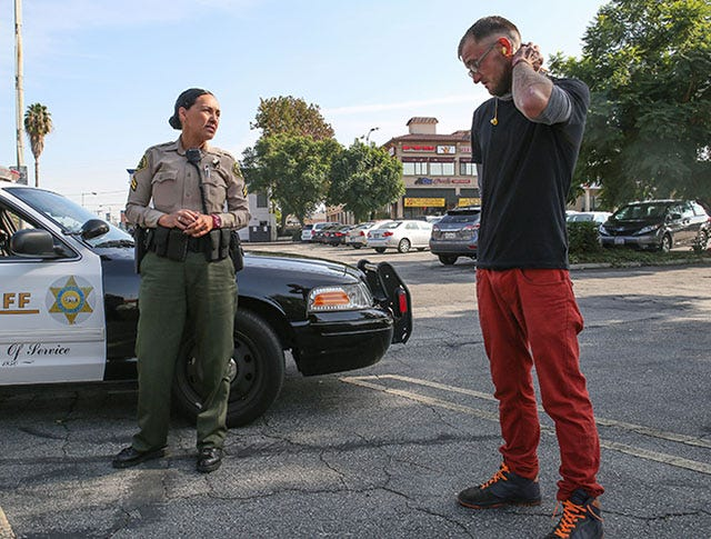 Los Angeles County Sheriff's deputy Joanne Arcos talks with Daniel Harris, who admits he likes to steal because it gives him a rush. Harris lives on the streets in Hacienda Heights, Calif., November 23, 2016. Jay Calderon/The Desert Sun
