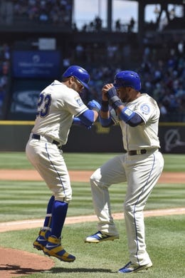 Jul 30, 2017; Seattle, WA, USA; Seattle Mariners designated hitter Nelson Cruz (23) and Seattle Mariners second baseman Robinson Cano (22) celebrate after Cruz hit a 3-run home run against the New York Mets during the first inning at Safeco Field. Mandatory Credit: Steven Bisig-USA TODAY Sports