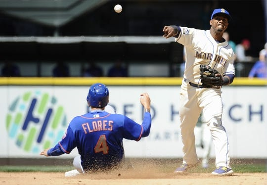 Jul 30, 2017; Seattle, WA, USA; Seattle Mariners shortstop Jean Segura (2) throws the ball to first base after the force out on New York Mets first baseman Wilmer Flores (4) during the fourth inning at Safeco Field. Mandatory Credit: Steven Bisig-USA TODAY Sports
