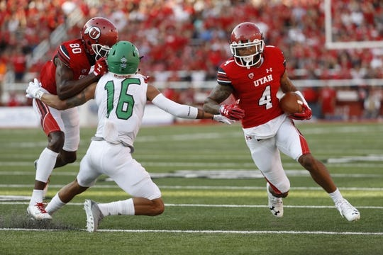 Aug 31, 2017; Salt Lake City, UT, USA; Utah Utes wide receiver Troy McCormick Jr. (4) runs the ball on a block by teammate wide receiver Siaosi Wilson (80) on North Dakota Fighting Hawks defensive back Torrey Hunt (16) in the first quarter at Rice-Eccles Stadium. Mandatory Credit: Jeff Swinger-USA TODAY Sports