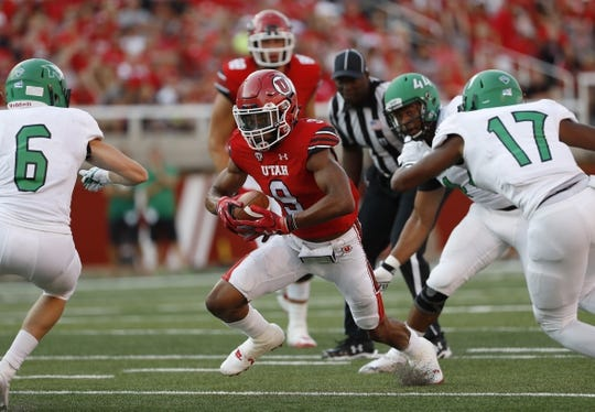 Aug 31, 2017; Salt Lake City, UT, USA; Utah Utes wide receiver Darren Carrington (9) runs the ball against North Dakota Fighting Hawks defensive back Evan Holm (6) defensive back Chuck Flowers (17) in the first quarter at Rice-Eccles Stadium. Mandatory Credit: Jeff Swinger-USA TODAY Sports