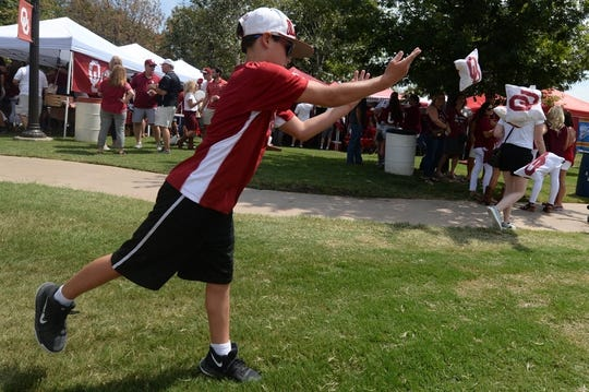 Sep 2, 2017; Norman, OK, USA; Joseph Ellenberg of Houston, Texas, plays cornhole at tailgate activities prior to action between the UTEP Miners and the Oklahoma Sooners at Gaylord Family - Oklahoma Memorial Stadium. Mandatory Credit: Mark D. Smith-USA TODAY Sports