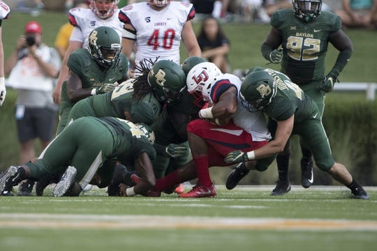 Sep 2, 2017; Waco, TX, USA; Liberty Flames running back Carrington Mosley (34) is brought down by the Baylor Bears defense during the first quarter at McLane Stadium. Mandatory Credit: Jerome Miron-USA TODAY Sports
