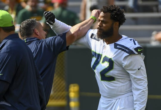 Sep 10, 2017; Green Bay, WI, USA;  Seattle Seahawks defensive end Michael Bennett (72) is greeted during warmups before the game against the Green Bay Packers at Lambeau Field. Mandatory Credit: Benny Sieu-USA TODAY Sports