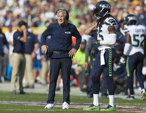 Sep 10, 2017; Green Bay, WI, USA; Seattle Seahawks head coach Pete Carroll talks with cornerback Richard Sherman (25) during an injury timeout during the second quarter against the Green Bay Packers at Lambeau Field. Mandatory Credit: Jeff Hanisch-USA TODAY Sports