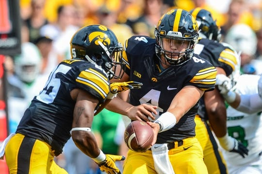 Sep 16, 2017; Iowa City, IA, USA; Iowa Hawkeyes quarterback Nathan Stanley (4) hands the ball off to running back Akrum Wadley (25) during the game against the North Texas Mean Green at Kinnick Stadium. Mandatory Credit: Jeffrey Becker-USA TODAY Sports