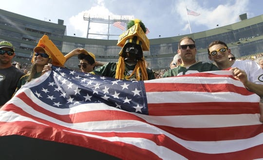 Sept 24, 2017; Green Bay, WS, USA; Green Bay Packers fans wave the American flag following the National Anthem prior to the game against the Cincinnati Bengals. Mandatory Credit: Mark Hoffman/Milwaukee Journal Sentinel via USA TODAY Sports