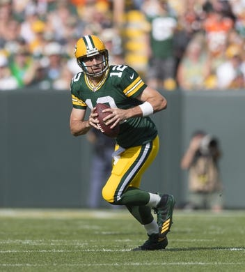 Sep 24, 2017; Green Bay, WI, USA; Green Bay Packers quarterback Aaron Rodgers (12) rolls out of the pocket during the first quarter against the Cincinnati Bengals at Lambeau Field. Mandatory Credit: Jeff Hanisch-USA TODAY Sports