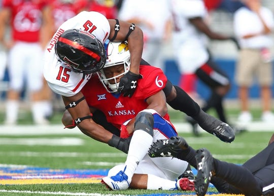 Oct 7, 2017; Lawrence, KS, USA; Kansas Jayhawks wide receiver Quan Hampton (6) is tackled by Texas Tech Red Raiders defensive back Vaughnte Dorsey (15) in the first half at Memorial Stadium. Mandatory Credit: Jay Biggerstaff-USA TODAY Sports