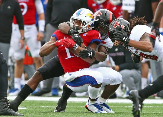 Oct 7, 2017; Lawrence, KS, USA; Kansas Jayhawks running back Khalil Herbert (10) is tackled by Texas Tech Red Raiders defensive back Vaughnte Dorsey (15) in the first half at Memorial Stadium. Mandatory Credit: Jay Biggerstaff-USA TODAY Sports
