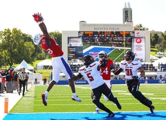 Oct 7, 2017; Lawrence, KS, USA; Kansas Jayhawks wide receiver Jeremiah Booker (88) catches a touchdown pass as Texas Tech Red Raiders defensive backs Octavious Morgan (5) and Justus Parker (31) defend in the first half at Memorial Stadium. Mandatory Credit: Jay Biggerstaff-USA TODAY Sports
