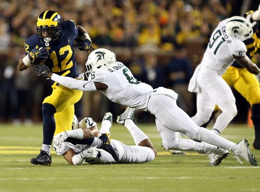 Oct 7, 2017; Ann Arbor, MI, USA; Michigan Wolverines running back Chris Evans (12) breaks tackle of Michigan State Spartans safety David Dowell (6) during the first quarter of a game at Michigan Stadium. Mandatory Credit: Mike Carter-USA TODAY Sports