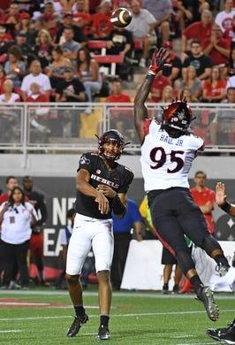 Oct 7, 2017; Las Vegas, NV, USA; UNLV Rebels quarterback Armani Rogers (1) throws over the reach of San Diego Aztecs defensive lineman Noble Hall (95) at Sam Boyd Stadium. Mandatory Credit: Stephen R. Sylvanie-USA TODAY Sports