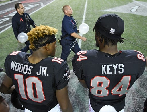 Oct 7, 2017; Las Vegas, NV, USA; UNLV Rebels wide receiver Darren Woods Jr. (10) and wide receiver Kendal Keys (84) stand as first responders walk onto the field carrying balloons representing the lives lost in the tragedy at Las Vegas before a game against the San Diego Aztecs at Sam Boyd Stadium. Mandatory Credit: Stephen R. Sylvanie-USA TODAY Sports