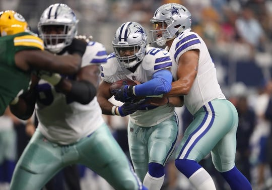 Oct 8, 2017; Arlington, TX, USA; Dallas Cowboys running back Ezekiel Elliott (21) takes the hand off from quarterback Dak Prescott (4) against the Green Bay Packers at AT&T Stadium. Mandatory Credit: Matthew Emmons-USA TODAY Sports