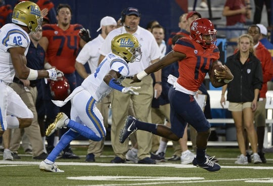 Oct 14, 2017; Tucson, AZ, USA; Arizona Wildcats quarterback Khalil Tate (14) runs the ball for a touchdown under pressure from UCLA Bruins defensive back Jaleel Wadood (4) during the first half against the UCLA Bruins at Arizona Stadium. Mandatory Credit: Casey Sapio-USA TODAY Sports