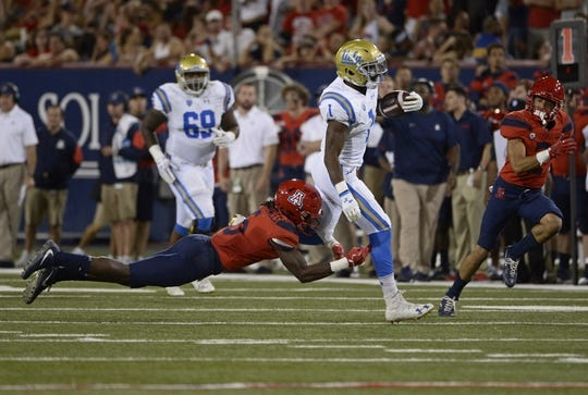 Oct 14, 2017; Tucson, AZ, USA; UCLA Bruins running back Soso Jamabo (1) runs the ball as he is tackled by Arizona Wildcats safety Demetrius Flannigan-Fowles (6) during the first half at Arizona Stadium. Mandatory Credit: Casey Sapio-USA TODAY Sports