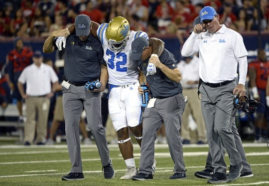 Oct 14, 2017; Tucson, AZ, USA; UCLA Bruins running back Jalen Starks (32) is helped off of the field during the first half against the Arizona Wildcats at Arizona Stadium. Mandatory Credit: Casey Sapio-USA TODAY Sports