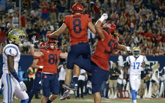 Oct 14, 2017; Tucson, AZ, USA; Arizona Wildcats tight end Bryce Wolma (81) tight end Trevor Wood (8) and offensive lineman Layth Friekh (58) celebrate a touchdown against the UCLA Bruins during the first half at Arizona Stadium. Mandatory Credit: Casey Sapio-USA TODAY Sports