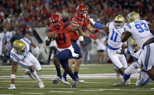 Oct 14, 2017; Tucson, AZ, USA; Arizona Wildcats quarterback Khalil Tate (14) runs the ball as UCLA Bruins linebacker Kenny Young (42) defends during the second half at Arizona Stadium. Mandatory Credit: Casey Sapio-USA TODAY Sports