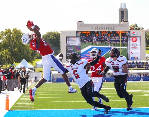 Oct 7, 2017; Lawrence, KS, USA; Kansas Jayhawks wide receiver Jeremiah Booker (88) catches a touchdown pass as Texas Tech Red Raiders defensive backs Octavious Morgan (5) and Justus Parker (31) defends in the first half at Memorial Stadium. Mandatory Credit: Jay Biggerstaff-USA TODAY Sports