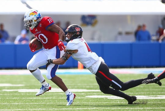 Oct 7, 2017; Lawrence, KS, USA; Kansas Jayhawks running back Khalil Herbert (10) is tackled by Texas Tech Red Raiders defensive back Desmon Smith (4) in the first half at Memorial Stadium. Mandatory Credit: Jay Biggerstaff-USA TODAY Sports