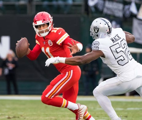 Oct 19, 2017; Oakland, CA, USA; Kansas City Chiefs quarterback Alex Smith (11) runs with the ball as Oakland Raiders defensive end Khalil Mack (52) defends during the first quarter at Oakland Coliseum. Mandatory Credit: Kelley L Cox-USA TODAY Sports