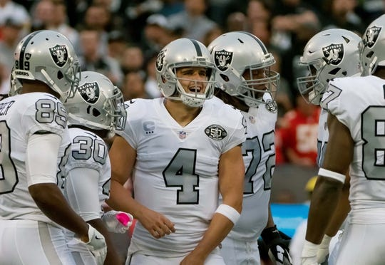 Oct 19, 2017; Oakland, CA, USA; Oakland Raiders quarterback Derek Carr (4) huddles with teammates against the Kansas City Chiefs during the first quarter at Oakland Coliseum. Mandatory Credit: Kelley L Cox-USA TODAY Sports