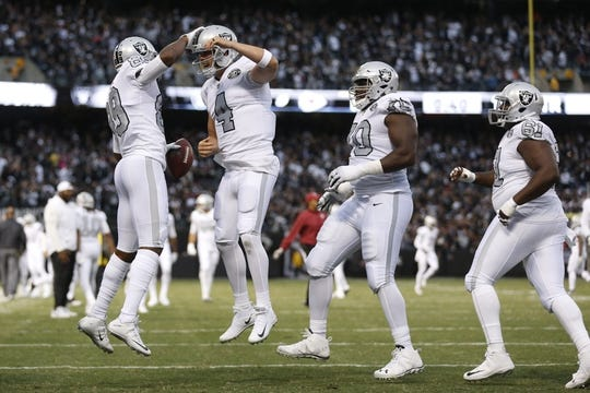 Oct 19, 2017; Oakland, CA, USA; Oakland Raiders wide receiver Amari Cooper (89) celebrates with quarterback Derek Carr (4) after catching a touchdown pass against the Kansas City Chiefs in the first quarter at Oakland Coliseum. Mandatory Credit: Cary Edmondson-USA TODAY Sports