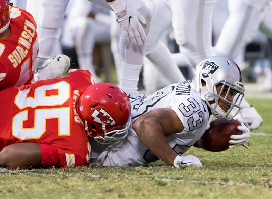 Oct 19, 2017; Oakland, CA, USA; Oakland Raiders running back DeAndre Washington (33) is brought down by Kansas City Chiefs defensive end Chris Jones (95) during the second quarter at Oakland Coliseum. Mandatory Credit: Kelley L Cox-USA TODAY Sports