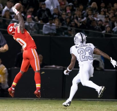 Oct 19, 2017; Oakland, CA, USA; Kansas City Chiefs wide receiver Tyreek Hill (10) catches the ball against Oakland Raiders cornerback Dexter McDonald (23) during the third quarter at Oakland Coliseum. Mandatory Credit: Kelley L Cox-USA TODAY Sports