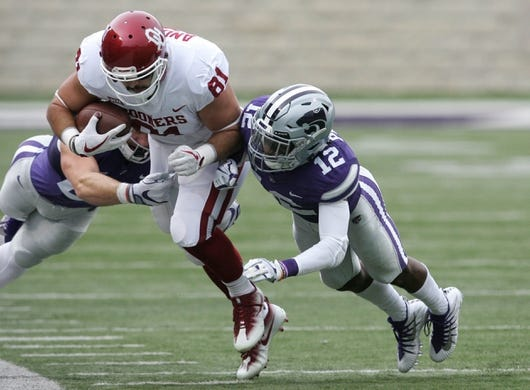 Oct 21, 2017; Manhattan, KS, USA; Oklahoma Sooners tight end Mark Andrews (81) is tackled by Kansas State Wildcats defensive backs AJ Parker (12) and Sean Newlan (29) during first quarter action at Bill Snyder Family Stadium. Mandatory Credit: Scott Sewell-USA TODAY Sports