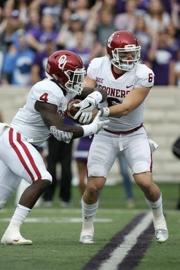 Oct 21, 2017; Manhattan, KS, USA; Oklahoma Sooners quarterback Baker Mayfield (6) fakes a handoff to running back Trey Sermon (4) during first-quarter action against the Kansas State Wildcats at Bill Snyder Family Stadium. The Sooners won the game 42-35. Mandatory Credit: Scott Sewell-USA TODAY Sports