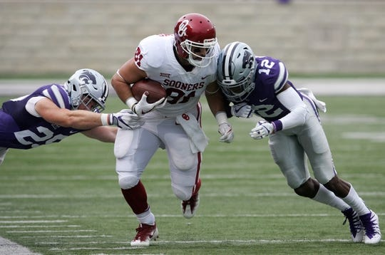 Oct 21, 2017; Manhattan, KS, USA; Oklahoma Sooners tight end Mark Andrews (81) is tackled by Kansas State Wildcats defensive backs AJ Parker (12) and Denzel Goolsby (20) during first-quarter action at Bill Snyder Family Stadium. The Sooners won the game 42-35. Mandatory Credit: Scott Sewell-USA TODAY Sports