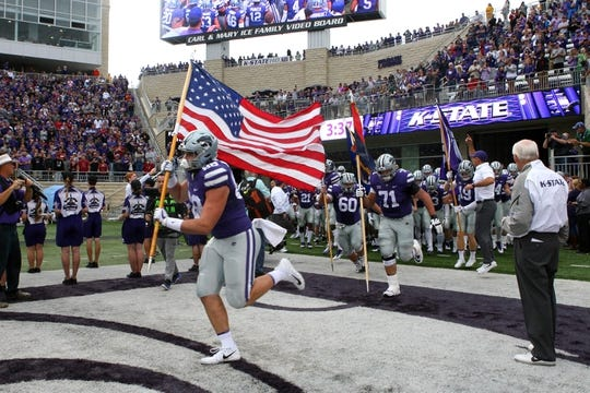 Oct 21, 2017; Manhattan, KS, USA; Kansas State Wildcats tight end Dayton Valentine (88) carries the American flag as he leads the Wildcats onto the field before the start of a game against the Oklahoma Sooners at Bill Snyder Family Stadium. The Sooners won the game 42-35. Mandatory Credit: Scott Sewell-USA TODAY Sports