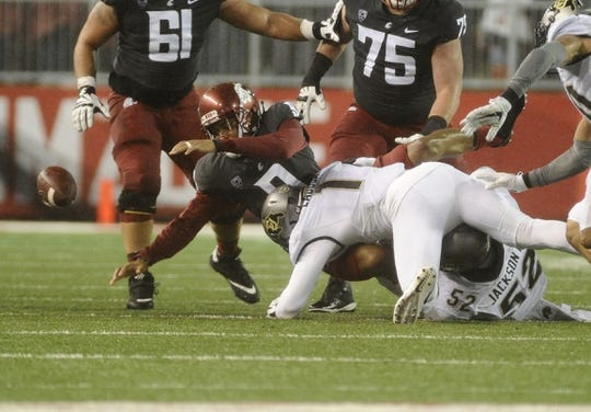 Oct 21, 2017; Pullman, WA, USA; Washington State Cougars wide receiver Tavares Martin Jr. (8) fumbles the ball after the hit by Colorado Buffaloes defensive end Leo Jackson III (52) and Colorado Buffaloes defensive back Afolabi Laguda (1) during the first half at Martin Stadium. Mandatory Credit: James Snook-USA TODAY Sports