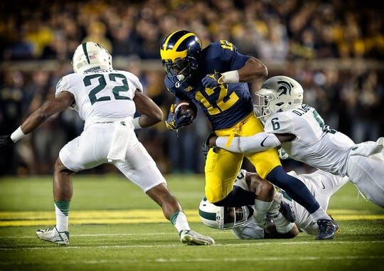 Oct 7, 2017; Ann Arbor, MI, USA; Michigan Wolverines running back Chris Evans (12) is tackled by Michigan State Spartans safety David Dowell (6) and Michigan State Spartans safety Khari Willis (27) during the first quarter of a game at Michigan Stadium. Mandatory Credit: Mike Carter-USA TODAY Sports