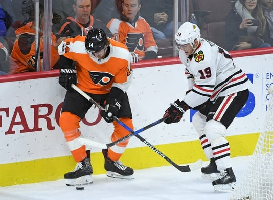 Nov 9, 2017; Philadelphia, PA, USA; Philadelphia Flyers center Sean Couturier (14) and Chicago Blackhawks center Jonathan Toews (19) battle for the puck during the third period at Wells Fargo Center. Mandatory Credit: Eric Hartline-USA TODAY Sports
