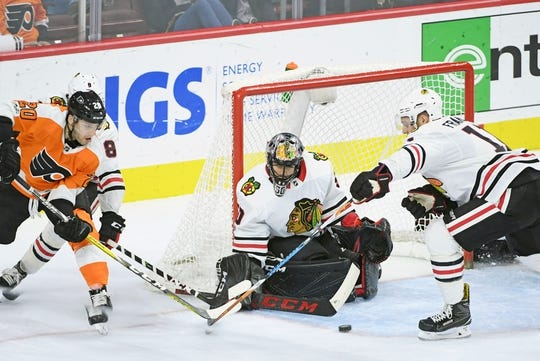 Nov 9, 2017; Philadelphia, PA, USA; Philadelphia Flyers left wing Taylor Leier (20) is defended by Chicago Blackhawks center Nick Schmaltz (8) and defenseman Cody Franson (11) in front of goalie Corey Crawford (50) during the third period at Wells Fargo Center. Mandatory Credit: Eric Hartline-USA TODAY Sports
