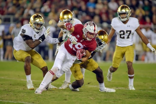 Nov 25, 2017; Stanford, CA, USA; Stanford Cardinal wide receiver JJ Arcega-Whiteside (19) gets tackled by Notre Dame Fighting Irish linebacker Te'von Coney (4) during the first quarter at Stanford Stadium. Mandatory Credit: Sergio Estrada-USA TODAY Sports