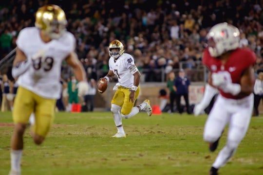 Nov 25, 2017; Stanford, CA, USA; Notre Dame Fighting Irish quarterback Brandon Wimbush (7) scrambles with the football during the second quarter against the Stanford Cardinal at Stanford Stadium. Mandatory Credit: Sergio Estrada-USA TODAY Sports