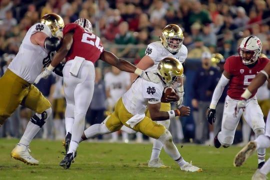 Nov 25, 2017; Stanford, CA, USA; Notre Dame Fighting Irish quarterback Brandon Wimbush (7) gets tackled by Stanford Cardinal linebacker Bobby Okereke (20) during the second quarter at Stanford Stadium. Mandatory Credit: Sergio Estrada-USA TODAY Sports