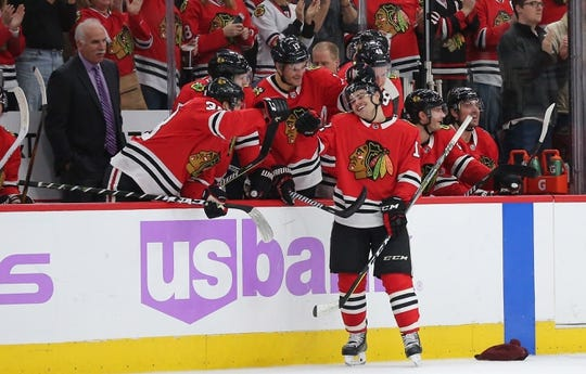Nov 27, 2017; Chicago, IL, USA; Chicago Blackhawks right wing Alex DeBrincat (12) is congratulated for scoring his third goal for a hat trick during the second period against the Anaheim Ducks at the United Center. Mandatory Credit: Dennis Wierzbicki-USA TODAY Sports